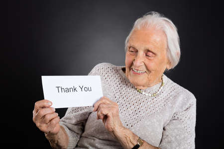 acknowledgment: Portrait Of Smiling Elder Woman Showing Thank You Card Over Grey Background
