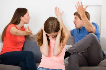 Menina virada cobrindo as orelhas na frente do Pais que têm o argumento