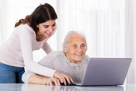 Mujer joven que ayuda a su abuela para usar una computadora portátil en el escritorio en el país