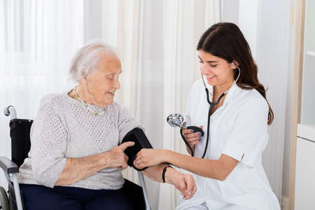 health professional: Happy Female Doctor Measuring Senior Patient Blood Pressure With Stethoscope In Hospital