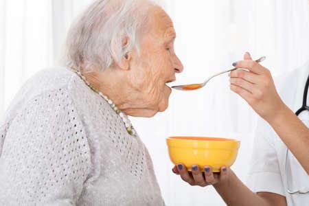 Close-up van de hand van de arts Feeding Soup To patiënt in het ziekenhuis