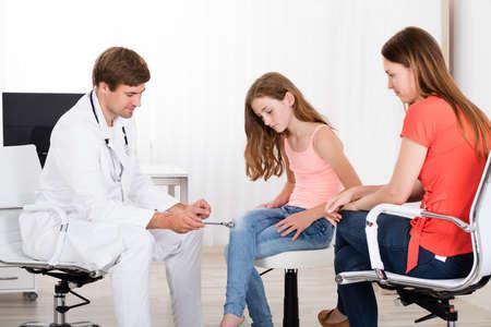 Jonge Mannelijke Neuroloog onderzoeken Knee Reflex On Girl In Clinic Stockfoto