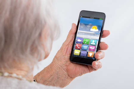 woman on phone: Close-up Of Senior Woman Holding Smartphone With Colorful Application Icons At Home