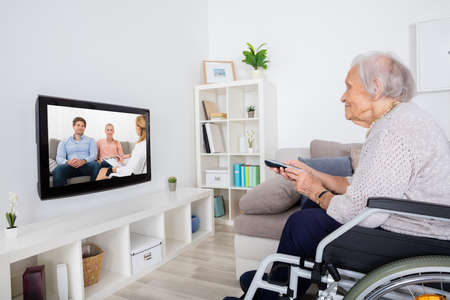 Grandmother On Wheelchair Watching Movie On Television At Home