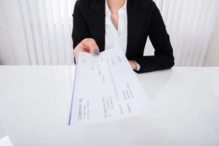 give: Photo Of Happy Businesswoman Offering Cheque In Office Stock Photo