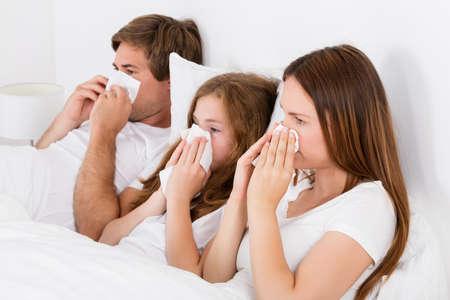 nariz: Familia que miente en cama sonarse la nariz Foto de archivo