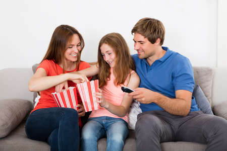 family sofa: Happy Family Sitting On Sofa Eating Popcorn At Home
