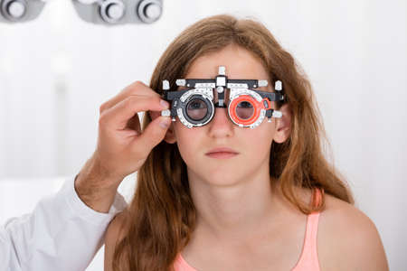 glasses eye: Close-up Of An Optometrist Checking Girls Vision With Trial Frame At Eye Clinic