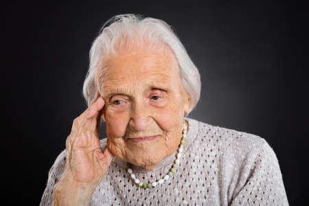 Portrait von nachdenklichen Ältere Frau über grauen Hintergrund