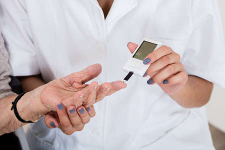 a medical examination: Close-up Of Doctor Holding Patients Finger Checking Sugar Level With Glucometer