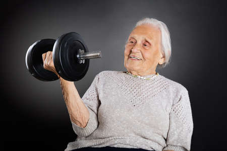 Happy Senior Woman Doing Exercise With Dumbbell Over Grey Background Stock Photo