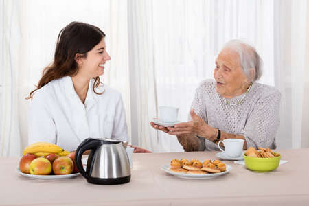 cherished: Elder Woman Offering Coffee To Nurse While Having Tea