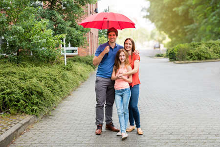 family life: Portrait Of A Young Couple With Their Daughter Holding Umbrella
