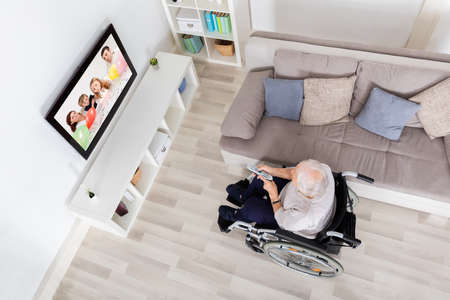 High Angle View Of Handicapped Grandmother Watching Movie On Television At Home photo