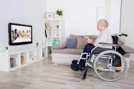 Grand-mère à regarder film à la télévision à la maison en fauteuil roulant