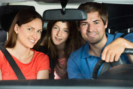 go inside: Happy Young Couple Driving In Car With Their Daughter
