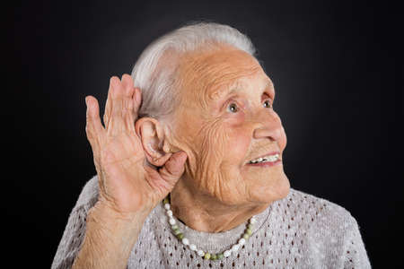 Happy Senior Woman Trying To Hear With Hand Over Ear Over Grey Background Stock Photo