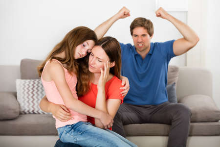 violent: Depressed Mother And Daughter In Front Of Violent Father Sitting On Sofa