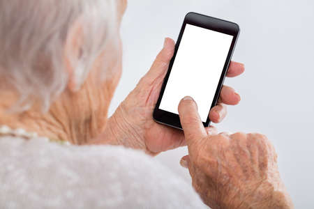 old hand: Close-up Of Senior Woman Using Smartphone With Blank Screen At Home