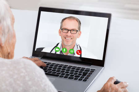 conferencing: Close-up Of Senior Woman Video Conferencing With Doctor On Laptop At Home Stock Photo