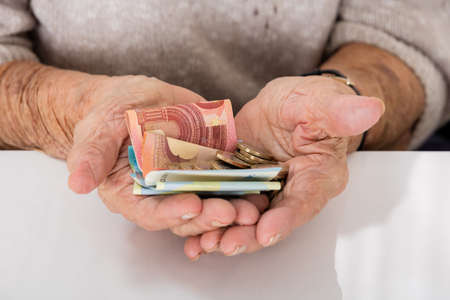 old hand: Close-up Of Senior Womans Hand Showing Money On Palm