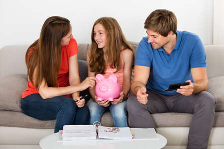 jeune fille adolescente: Sitting Happy Family Sur Sofa Calcul Bills At Home Banque d'images
