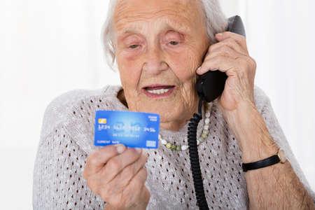 携帯電話でクレジット カードの詳細を与える年配の女性の肖像画 写真素材 - 64951212