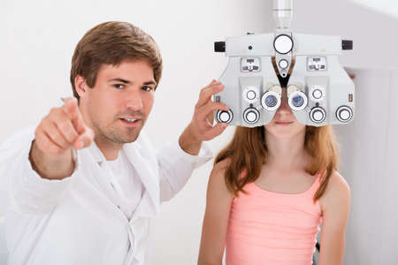 medical exam: Young Male Optometrist Checking Girls Vision With Phoropter