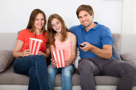 family sofa: Smiling Family With Popcorn Sitting On Sofa Watching Television Stock Photo