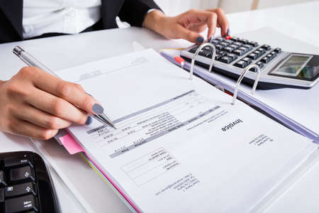 quantity: Close-up Of Businesswoman Hand Calculating Invoice Using Calculator At Desk In Office
