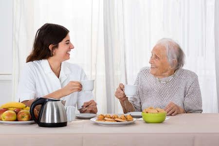 caretaker: Elder Woman Enjoying Tea With Her Caretaker Stock Photo