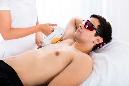 underarms: Young Man Receiving Laser Epilation Treatment On Underarms In Spa