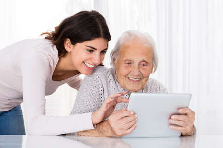 using tablet: Young Woman Helping Her Grandmother For Using A Digital Tablet On Desk At Home