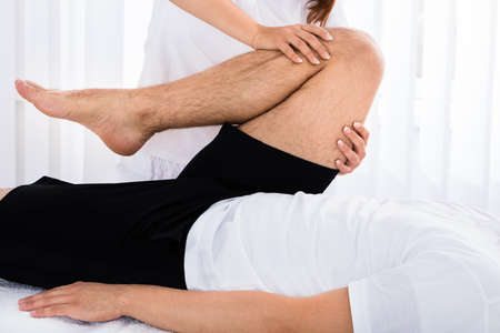Close-up Of A Masseur Giving Leg Massage To Man In Spa Stock Photo
