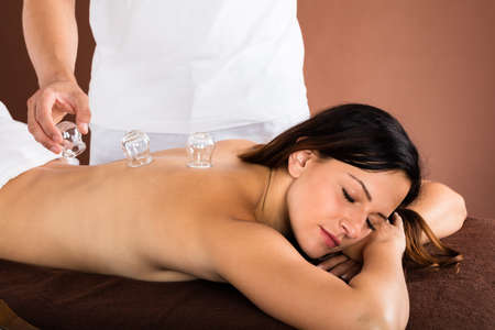 cupping therapy: Happy Young Woman Receiving Cupping Treatment On Back In Spa