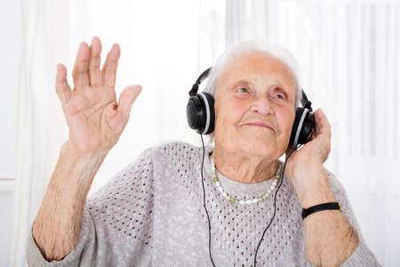 家でヘッドフォンで音楽を楽しむ幸せな年配の女性の肖像画