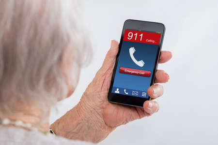 emergency number: Close-up Of Senior Woman Dialing Emergency Call On Mobilephone At Home