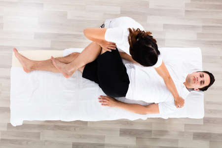 High Angle View Of A Young Female Therapist Massaging Relaxed Man's Leg Stock Photo - 64951265
