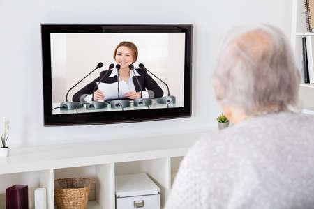 ver tv: Primer plano de la abuela ver las noticias en la televisión en el hogar