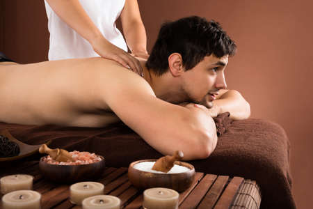 Young Man Receiving Shoulder Massage From Therapist In Spa