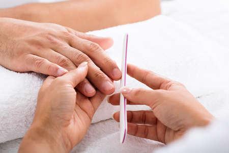 Close-up Of A Manicurist Filing Person's Nails In Salon Foto de archivo