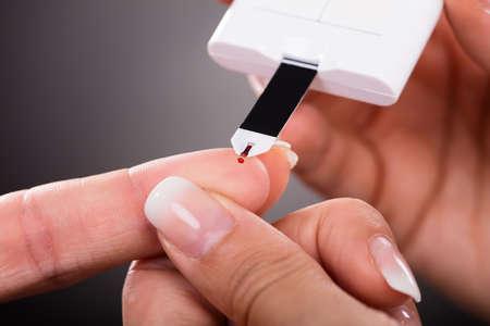 pacientes: Primer plano del nivel de azúcar Un Doctor en control del paciente con glucómetro