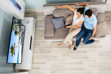 beach view: High Angle View Of Young Couple Watching Movie On Television At Home