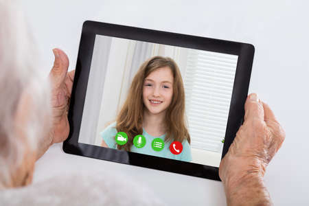 conferencing: Close-up Of Grandmother Video Conferencing On Digital Tablet With Her Granddaughter At Home Stock Photo