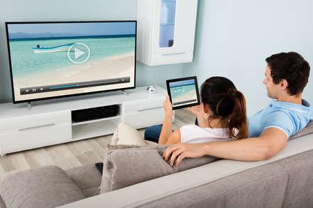 Jong koppel aansluiten TV Channel via Wi-Fi op digitale tablet thuis
