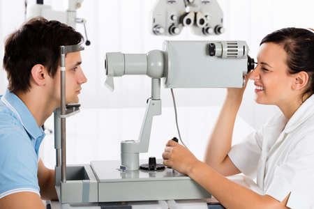 optometrist: Happy Young Female Optometrist Doing Vision Testing For Male Patient