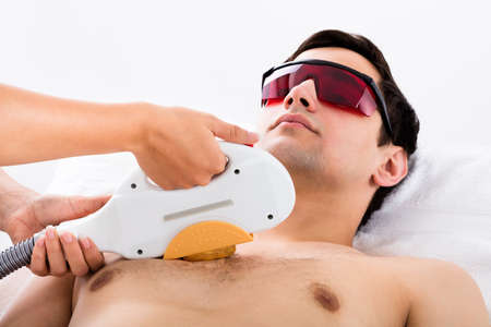 Therapist Giving Laser Epilation Treatment To Young Man In Spa Banque d'images
