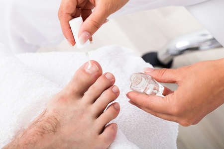 toenail: Close-up Of A Manicurist Applying Moisturizing Nail Oil On Persons Toenail