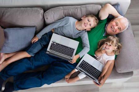 laptop computers: High Angle View Of Grandfather With Kids And Laptop Computers At Home