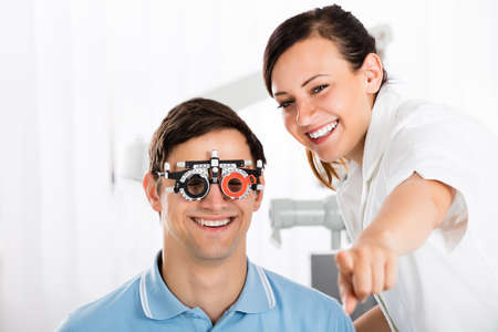 Young Smiling Female Optometrist Examining Patients Vision With Trial Frame Stock Photo